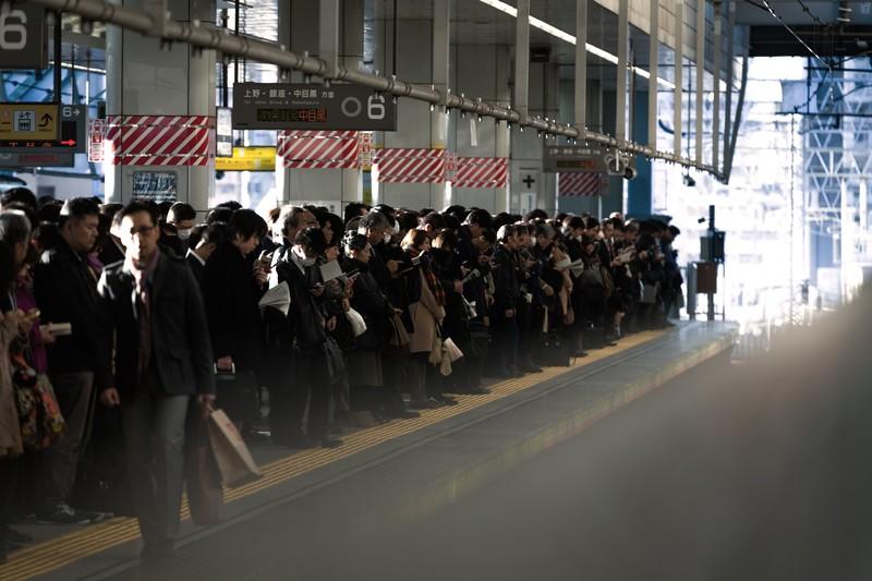 ラッシュのホームで電車を待つサラリーマンたち